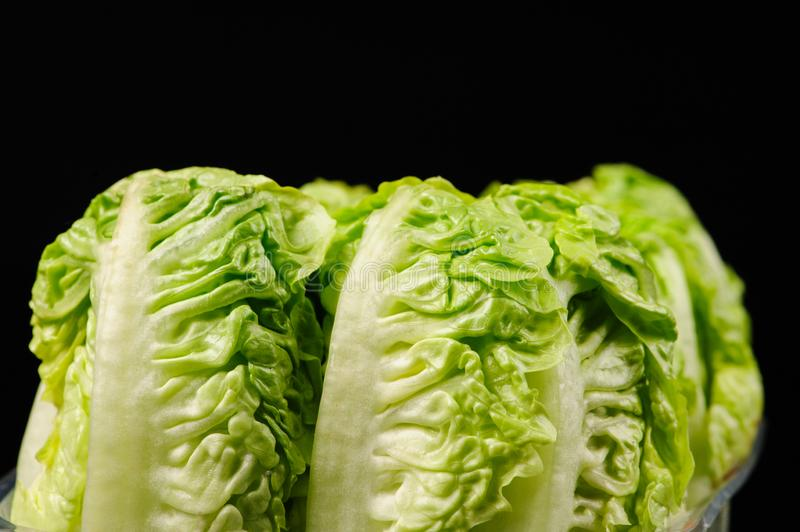 Fresh green salad. On the black background, organic, ingredient, vegetable, lettuce, food, vitamin, healthy, leaf, vegetarian, freshness, raw, nutrition royalty free stock photography