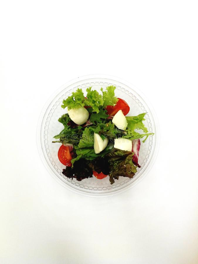 Fresh green salad. With cheesr tomato and iceberg salad on the white background stock images