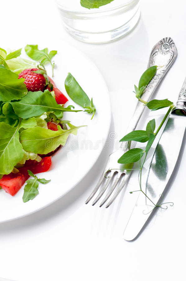 Fresh green salad with ripe tomatoes, pods of green peas and slices of strawberry. stock photos