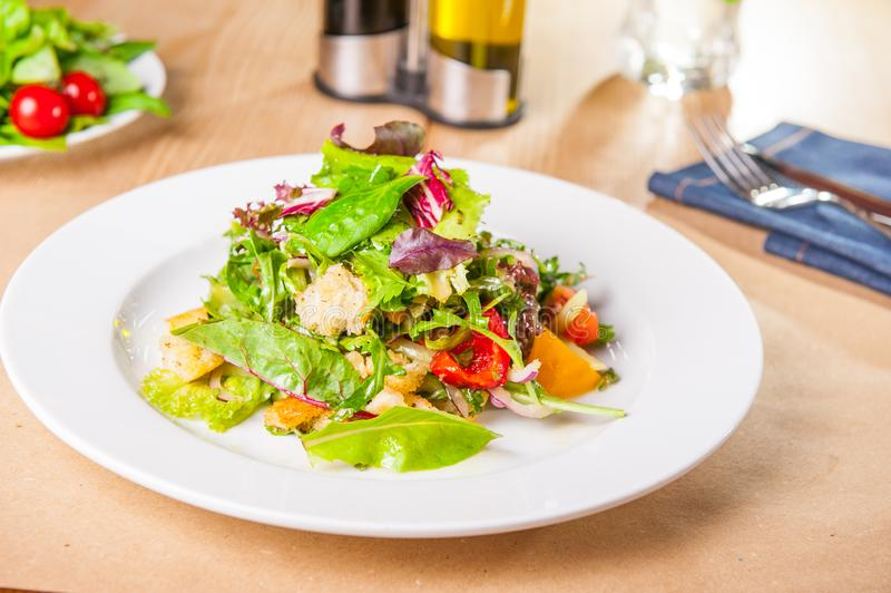 Fresh green salad with spinach,arugula,romaine, lettuce, beet leaves, bell pepper and croutons on the wooden served table. Healthy. Vegetarian food. Selective stock photos