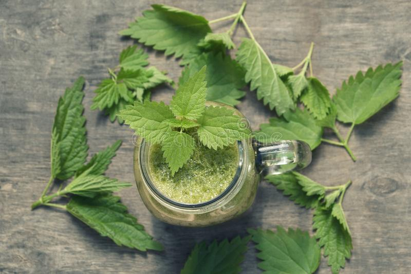 Fresh green smoothie with wild nettle and other herbs in mason jar. Fresh green smoothie with wild nettle and other herbs in mason jar on rustic wooden stock photos
