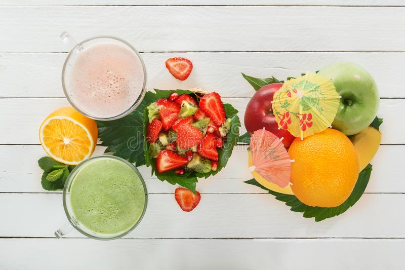 Fresh green smoothies and a milkshake of strawberries in glass glasses with tropical fruits on white boards stock image