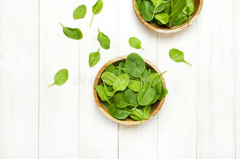 Fresh green spinach leaves on wooden bowl on white wooden rustic background top view copy space. Baby young spinach leaves, royalty free stock photography