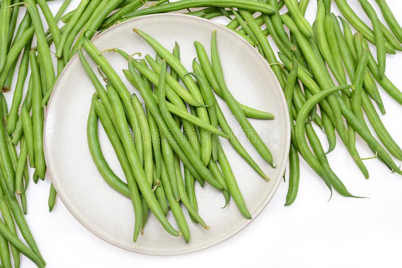 Fresh green string beans on a plate isolated on a white background. Empty space for text royalty free stock photo