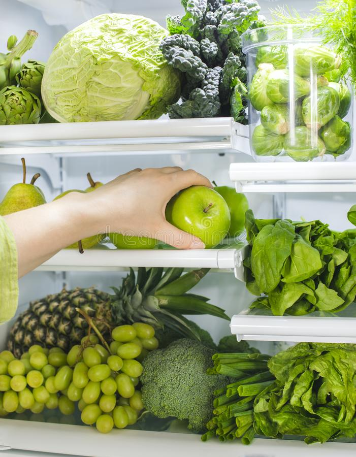 Fresh green vegetables and fruits in fridge. Woman takes the green apple from the open refrigerator. royalty free stock photos