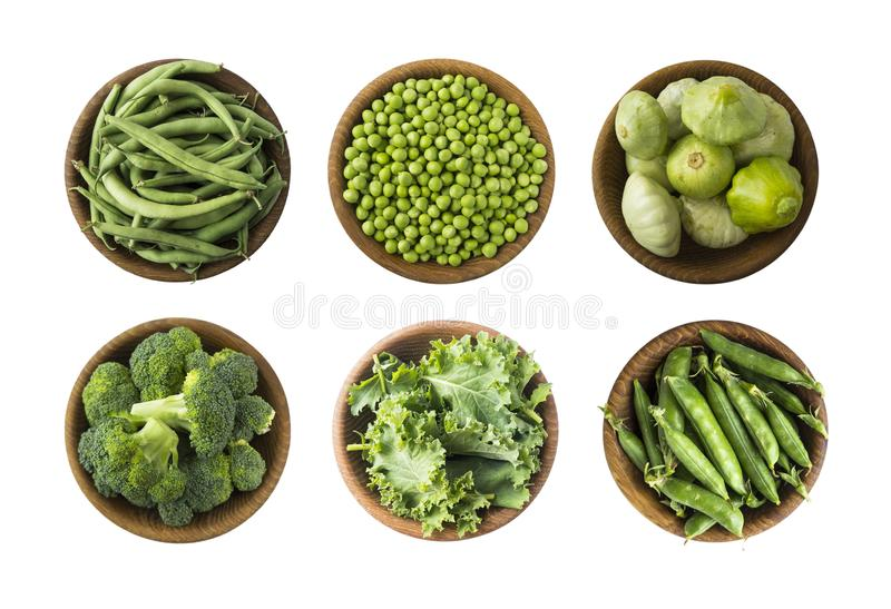 Fresh green vegetables isolated on a white background. Squash, green peas, broccoli, kale leaves and green bean in wooden bowl. Ve stock image