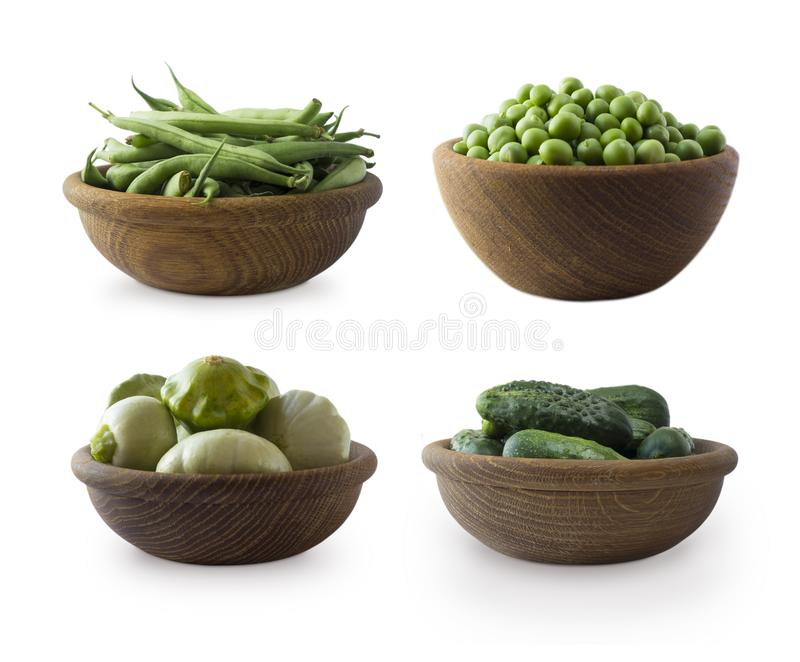 Fresh green vegetables isolated on a white background. Squash, green peas, cucumbers and green bean in wooden bowl. Vegetables wit stock photography