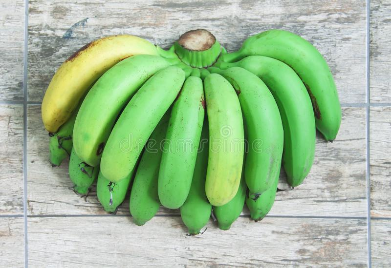 Fresh green and yellow bananas fruit group  Gros Michel   on wood table background top view. Close up Fresh green and yellow bananas fruit group  Gros Michel royalty free stock photo