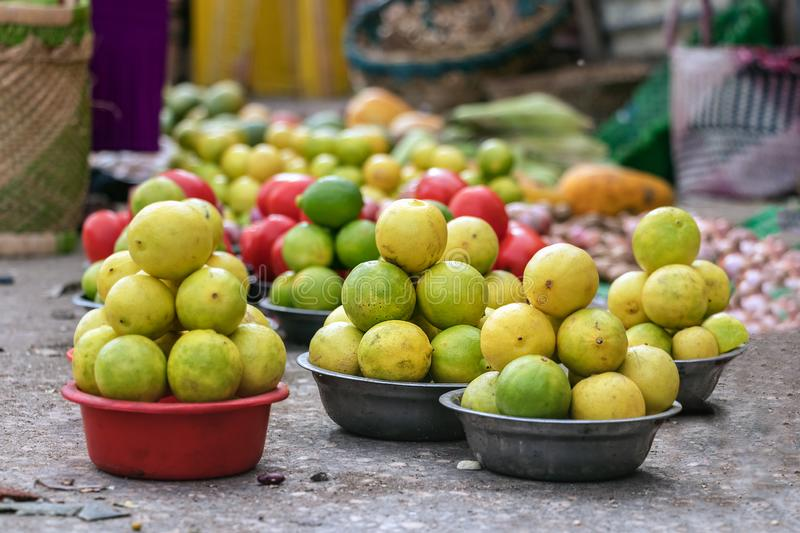 Fresh green and yellow lemons placed on baskets on the floor at the street market of Toliara, Madagascar stock photos