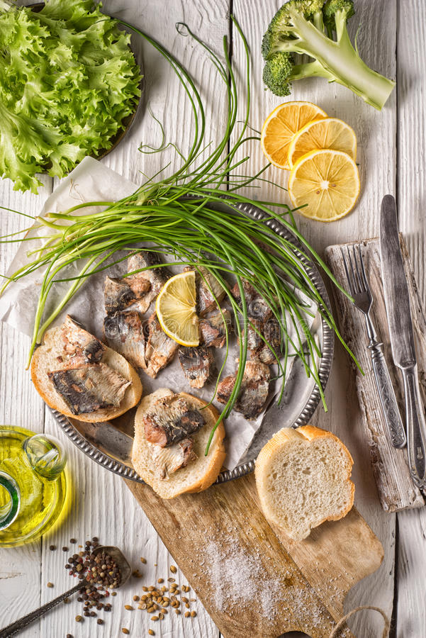 Fresh greens, sardines, bread on a wooden table. Vertical royalty free stock photo