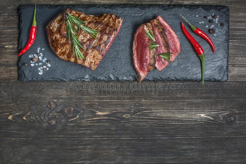 Fresh grilled meat. Grilled beef steak medium rare on wooden cutting board. Top view. royalty free stock photos