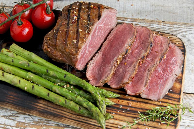 Fresh grilled meat.Grilled beef steak slicing medium rare , asparagus, tomato royalty free stock photography