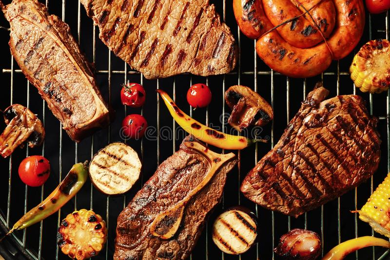 Fresh grilled meat steaks and vegetables on barbecue grate. Top view royalty free stock image