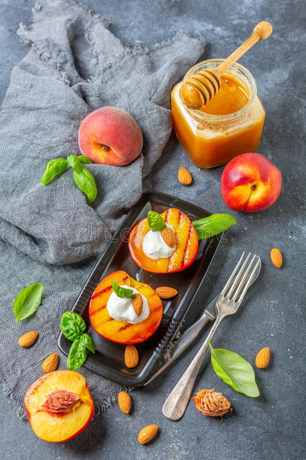 Fresh grilled peaches with honey and green basil. Plate with fried honey peaches with almonds, yogurt and green basil, jar of honey and cutlery on on a textured royalty free stock photography