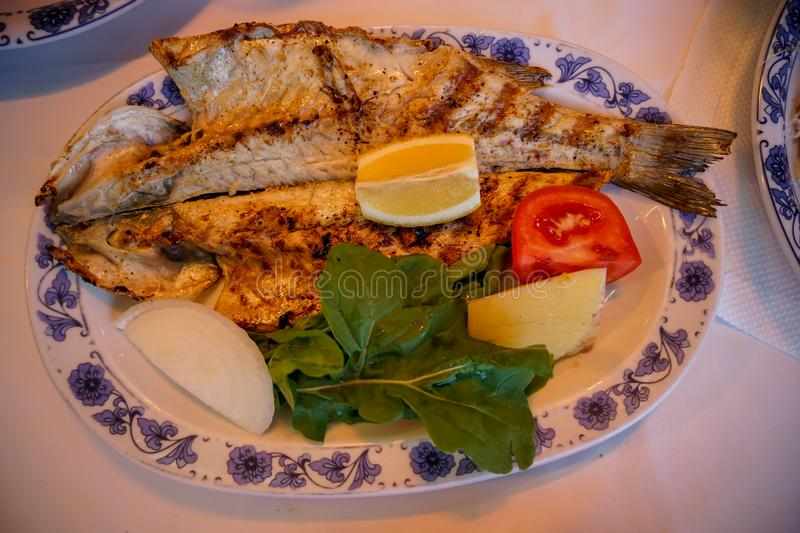 Fresh grilled whole sea bass fish with roasted potato, green salad, tomato and yellow lime on white oval plate with blue pattern stock image