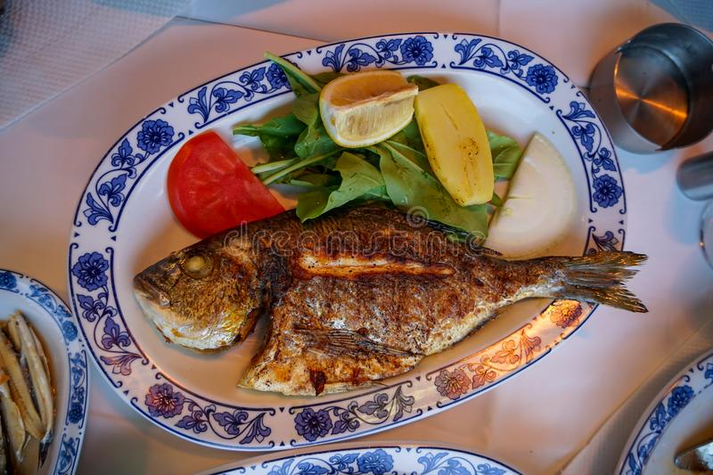 Fresh grilled whole sea bream fish with roasted potato, green salad, tomato and yellow lime on white oval plate with blue pattern royalty free stock images