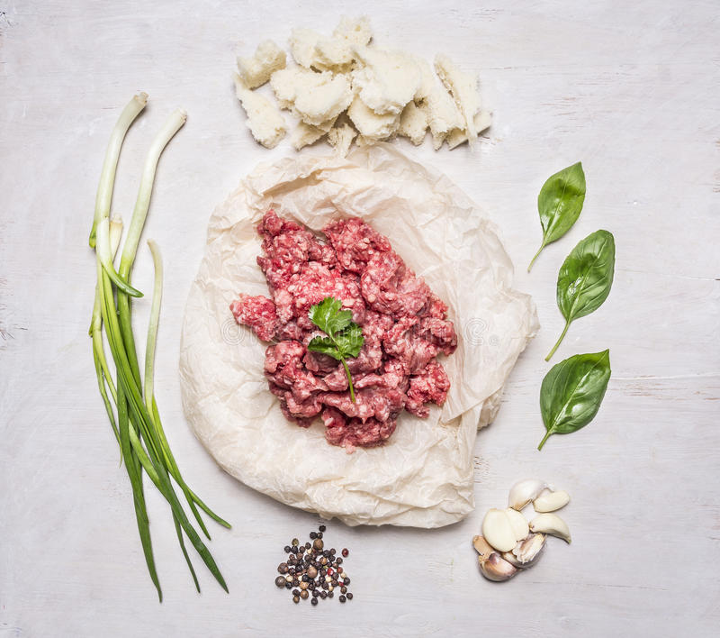 Fresh ground beef on a paper, with oregano, chives and pepper and garlic wooden rustic background top view. Fresh ground beef on a paper, with oregano, chives stock image