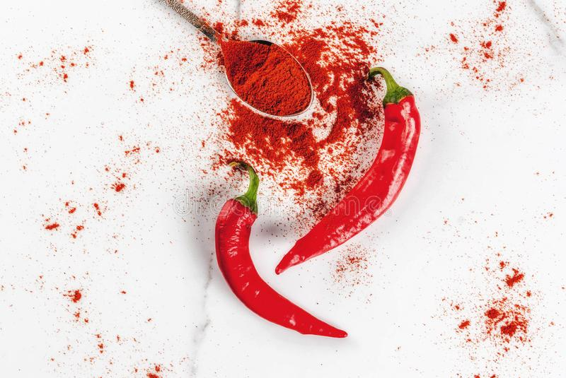 Fresh and ground chili pepper. Raw fresh organic and dried ground chili pepper on white marble background top view copy space royalty free stock photo