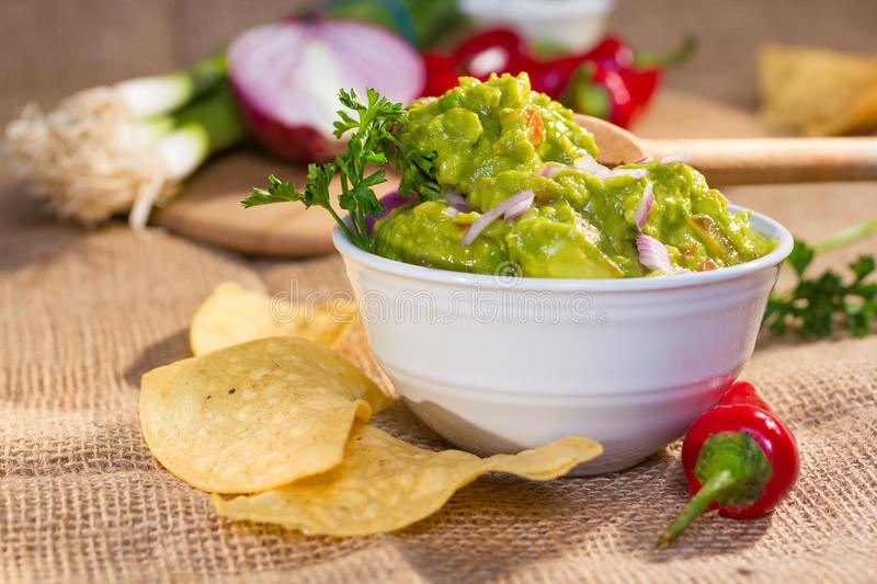 Fresh guacamole. Southwest guacamole served with corn chips and pepper stock photo