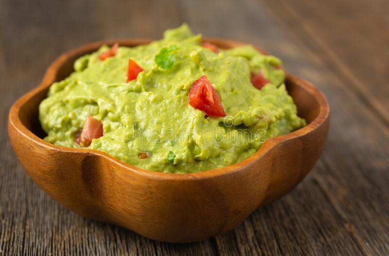 Fresh guacamole in a wooden bowl stock images