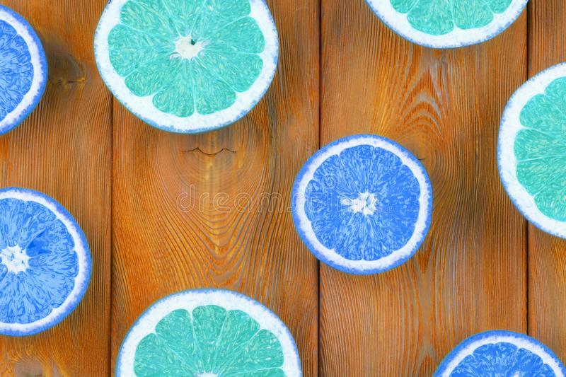 Fresh half cut grapefruit and orange on a blue wooden background, close up view. stock photography
