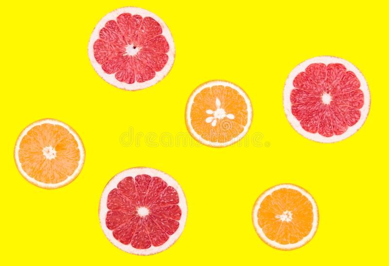 Fresh half cut grapefruit and orange isolated on yellow background. Close up view. Fruit concept. Healthy lifestyle concept.  stock photo
