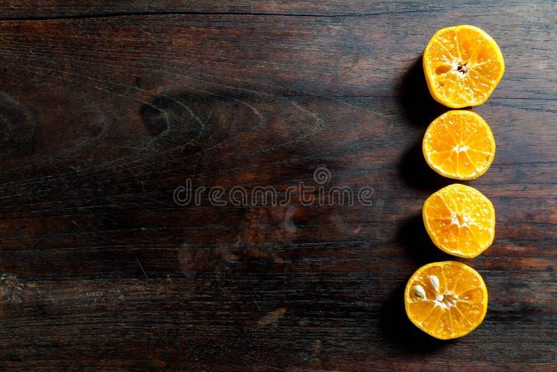Fresh half cut oranges on dark wooden table royalty free stock photography