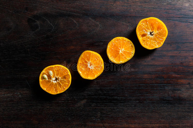 Fresh half cut oranges on dark wooden table royalty free stock images
