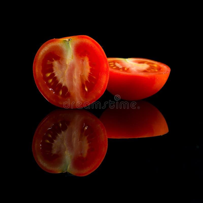 Fresh halfed red tomato. On black background royalty free stock image