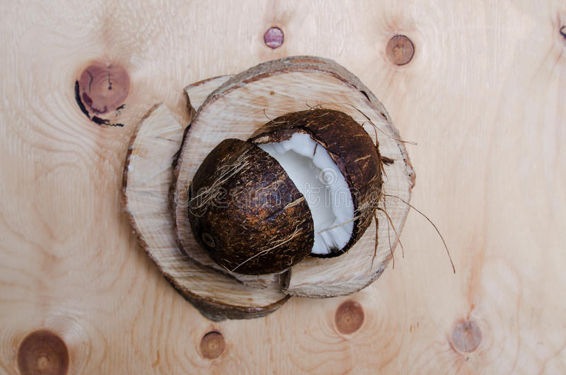 Fresh halved coconut on light wooden background. Organic healthy food concept. Beauty and SPA. Eco nature style. Rustic stock images