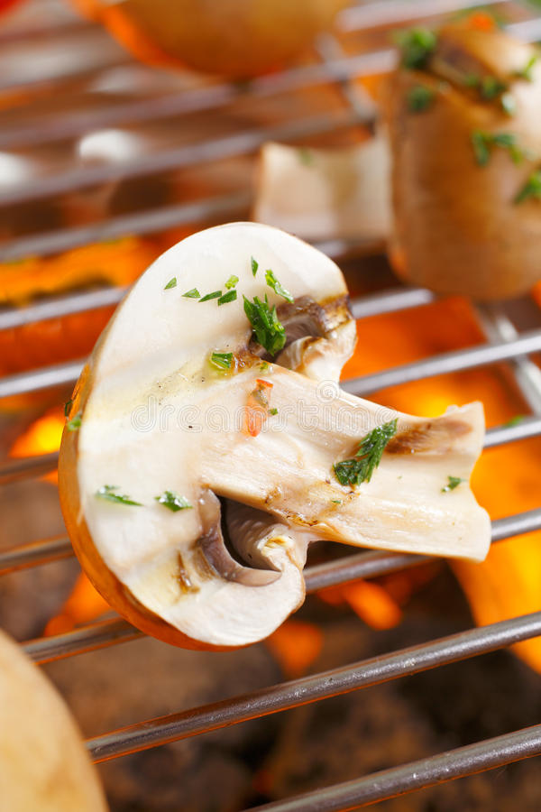 Mushrooms grilling over a barbecue. Fresh halved mushrooms sprinkled with chopped herbs for flavouring grilling over a barbecue fire royalty free stock image
