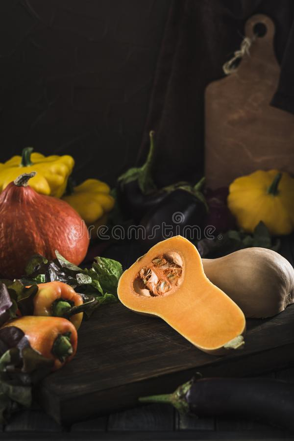 Fresh harvest of vegetables from pumpkin, eggplant, pepper, lettuce, red onion and squash on a dark wooden background stock photo