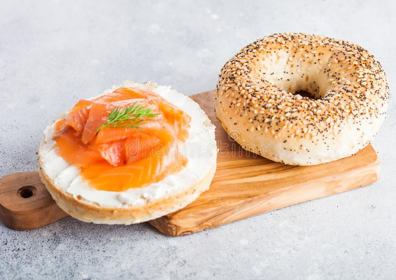 Fresh healthy bagel sandwich with salmon, ricotta and dill on vintage chopping board on light kitchen table background. Healthy di stock photos