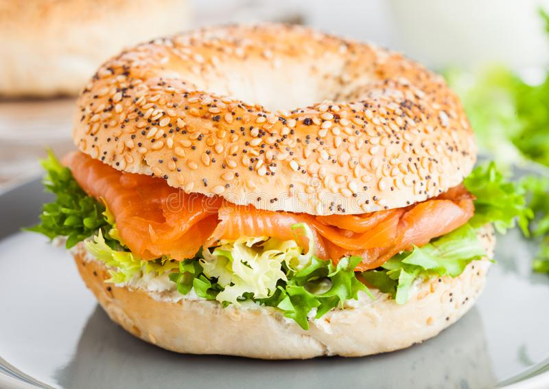 Fresh healthy bagel sandwich with salmon, ricotta and lettuce in grey plate on light kitchen table background. Healthy diet food. stock photos
