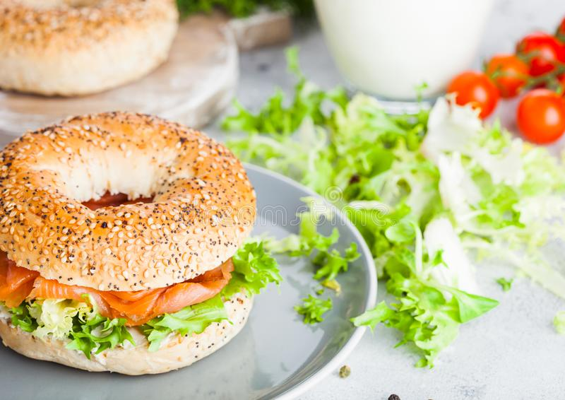 Fresh healthy bagel sandwich with salmon, ricotta and lettuce in grey plate on light kitchen table background. Healthy diet food. stock image