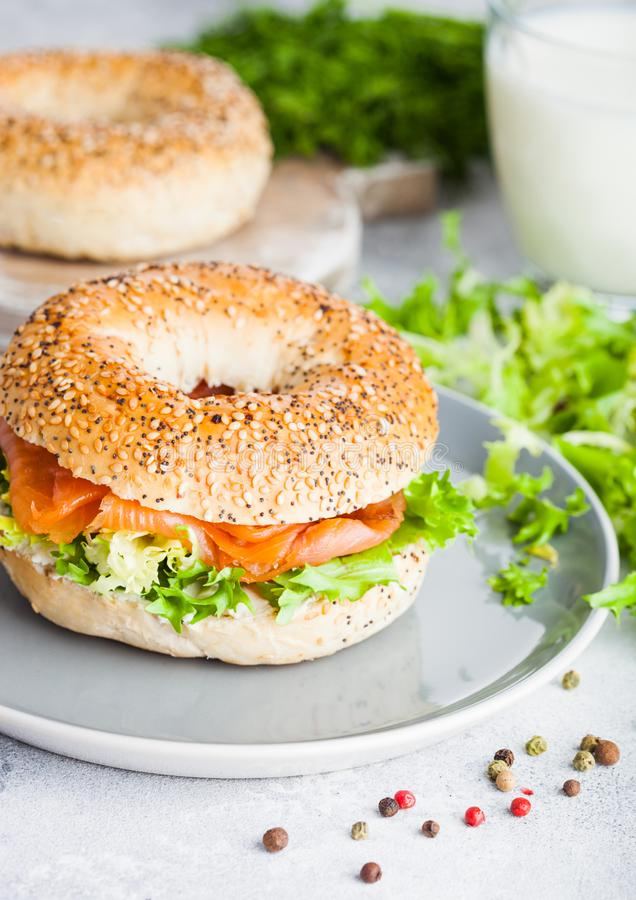 Fresh healthy bagel sandwich with salmon, ricotta and lettuce in grey plate on light kitchen table background. Healthy diet food. stock images