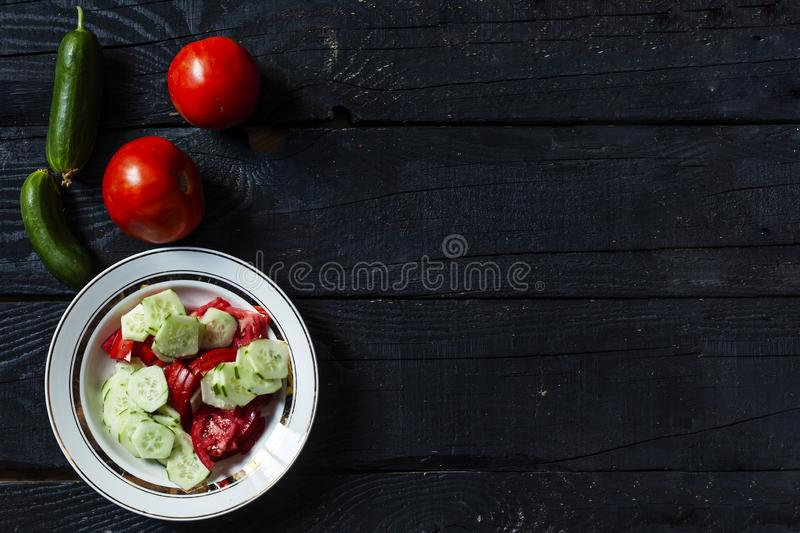Fresh healthy cucumber and tomato salad. Plate of fresh healthy cucumber and tomato salad on black wooden desk. Top view royalty free stock image