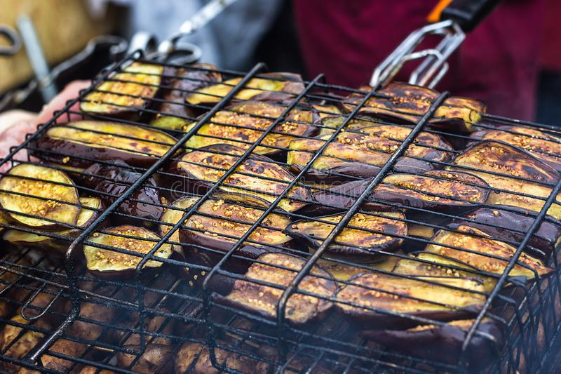 Fresh healthy eggplant or aubergine preparing on a barbecue grill over charcoal. Grilled aubergines eggplants slices. Vegetarian, royalty free stock photos
