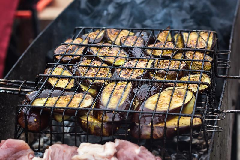 Fresh healthy eggplant or aubergine preparing on a barbecue grill over charcoal. Grilled aubergines eggplants slices. Vegetarian,. Mediterranean cuisine royalty free stock photo