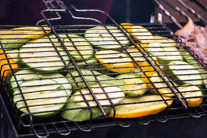 Fresh healthy green zucchini courgettes cucumber preparing on a barbecue grill over charcoal. Grilled zucchini slices. Vegetarian,. Mediterranean cuisine stock photo