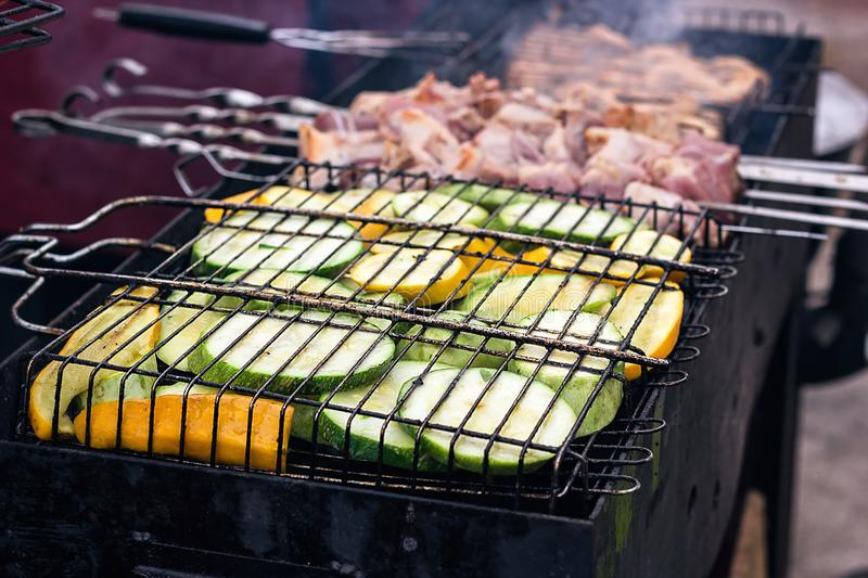 Fresh healthy green zucchini courgettes cucumber preparing on a barbecue grill over charcoal. Grilled zucchini slices. Vegetarian,. Mediterranean cuisine royalty free stock photo