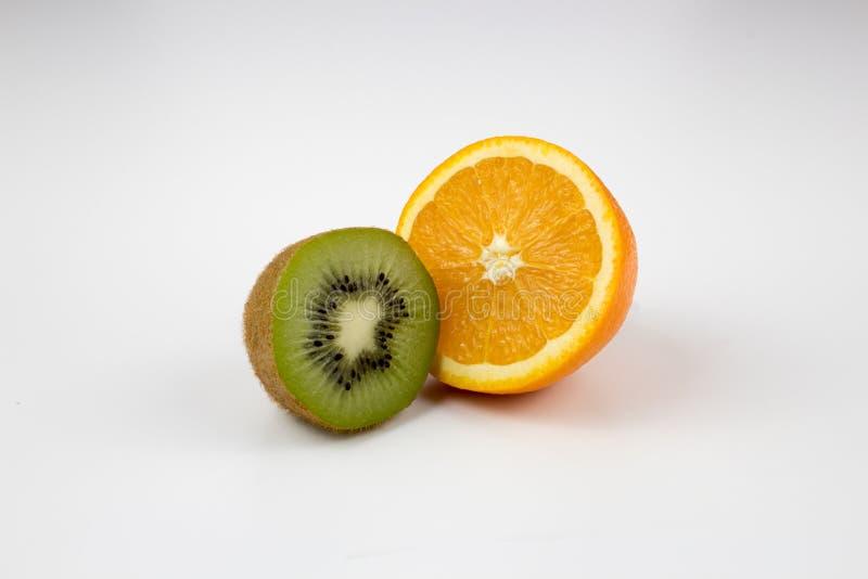 Half kiwi and half orange on background. Fresh, healthy, half ripe kiwi with a half orange on white background. multiple uses are possible royalty free stock photos