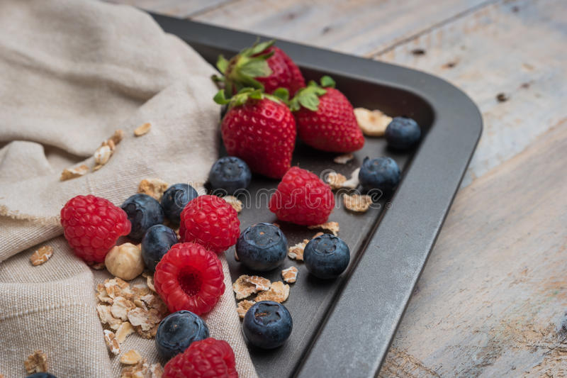 Fresh healthy ingredients for breakfast or smoothie on dark vintage board. Blueberries, raspberries and strawberries. Summer and stock photography