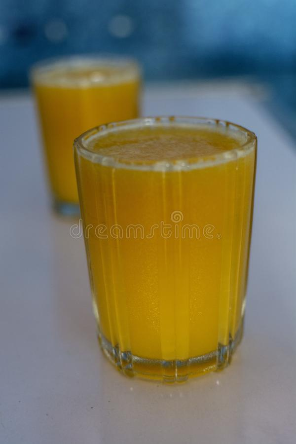 Fresh and healthy orange juice filled glass on white table stock image