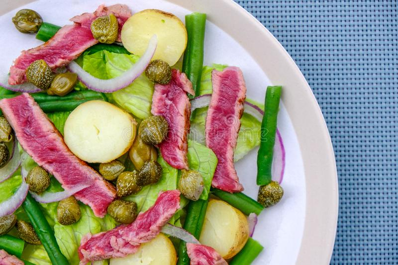 Fresh Healthy Rare Beef Steak Salad. With Capers, Boiled Potatoes, Green Beans and Red Onions stock image
