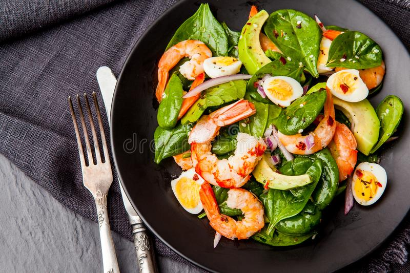 Fresh, healthy salad with shrimps, spinach and avocado on a black background. Top view. royalty free stock images