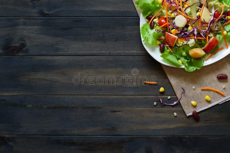 Fresh healthy salad on white plate with mixed greens vegetables, cereal, carrot, corn, pivot and red beans on wooden background royalty free stock images