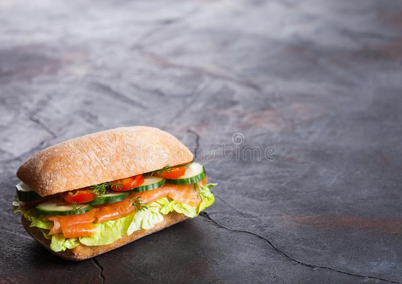 Fresh healthy salmon sandwich with lettuce and cucumber on black stone background. Breakfast snack. Space for text stock photography