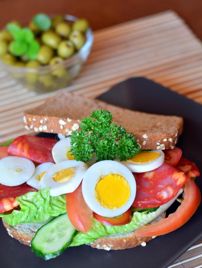 Fresh and healthy sandwich with salami and vegetables on a plate stock photos