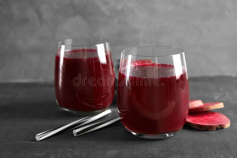 Fresh healthy smoothie in glasses with straws and slices of beets royalty free stock photos